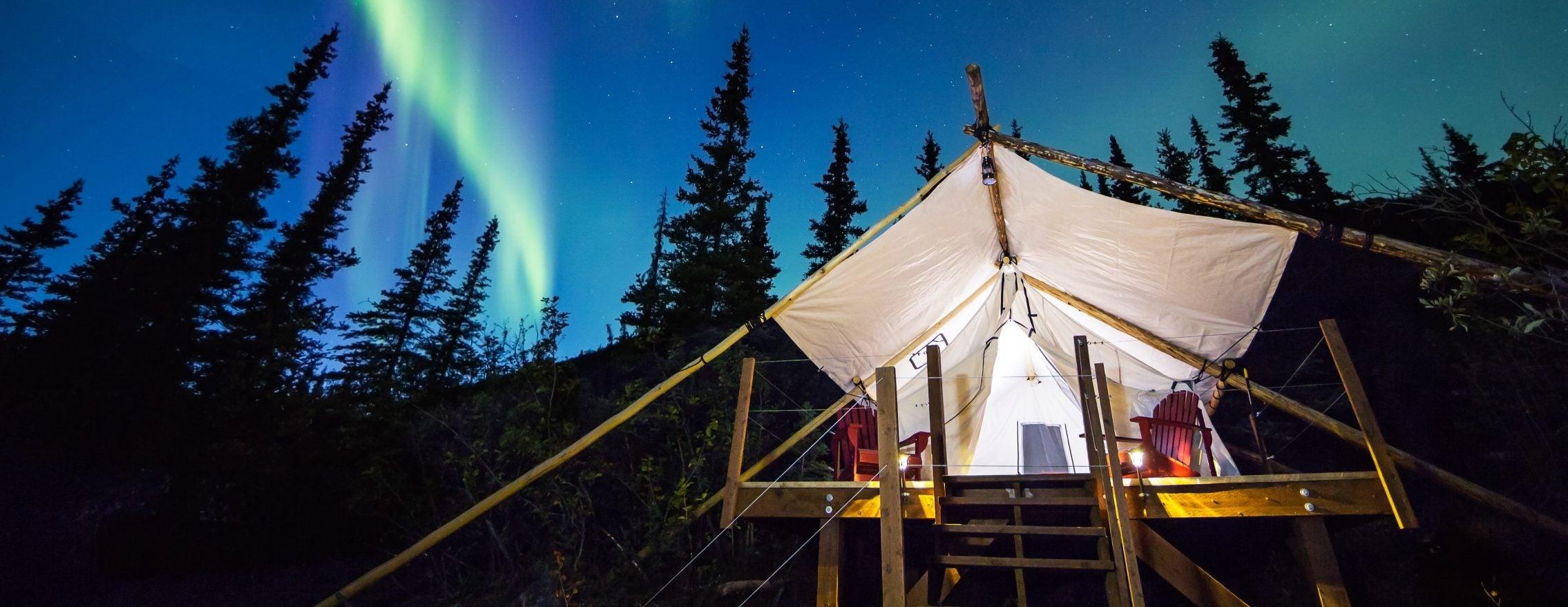 northern lights illuminate the sky above an eco-resort
