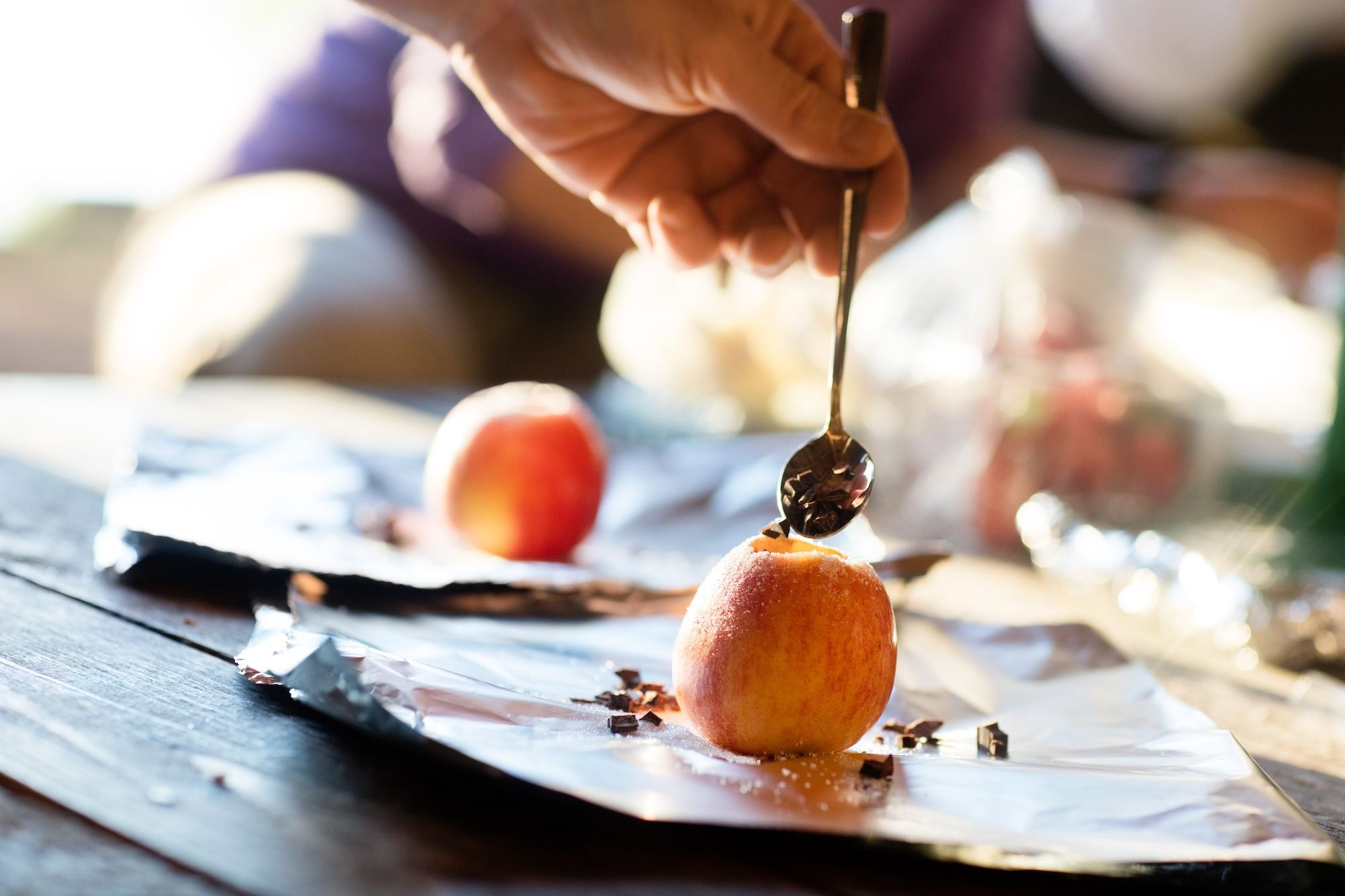 stuffing chocolate into campfire baked apples with a spoon