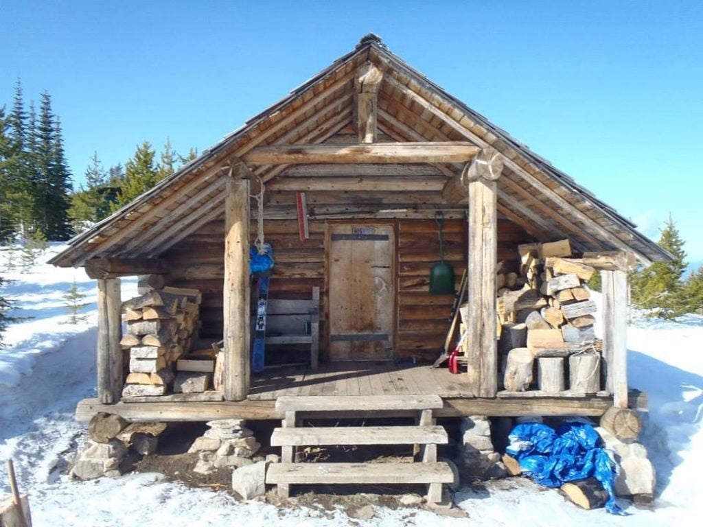 Cabin in the winter with chopped wood on the porch and snow on the ground