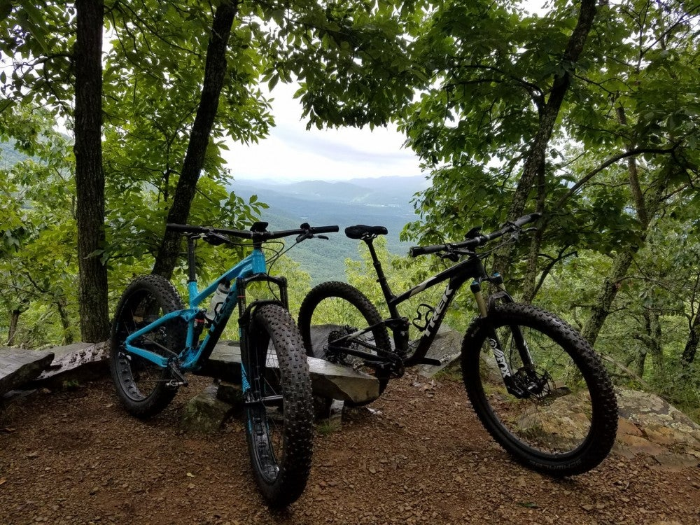 two mountain bikes rest near an overlook at douthat state park