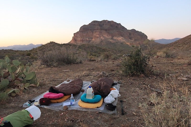rocky landscape showing an outdoor sleep setup for hikers in the foreground