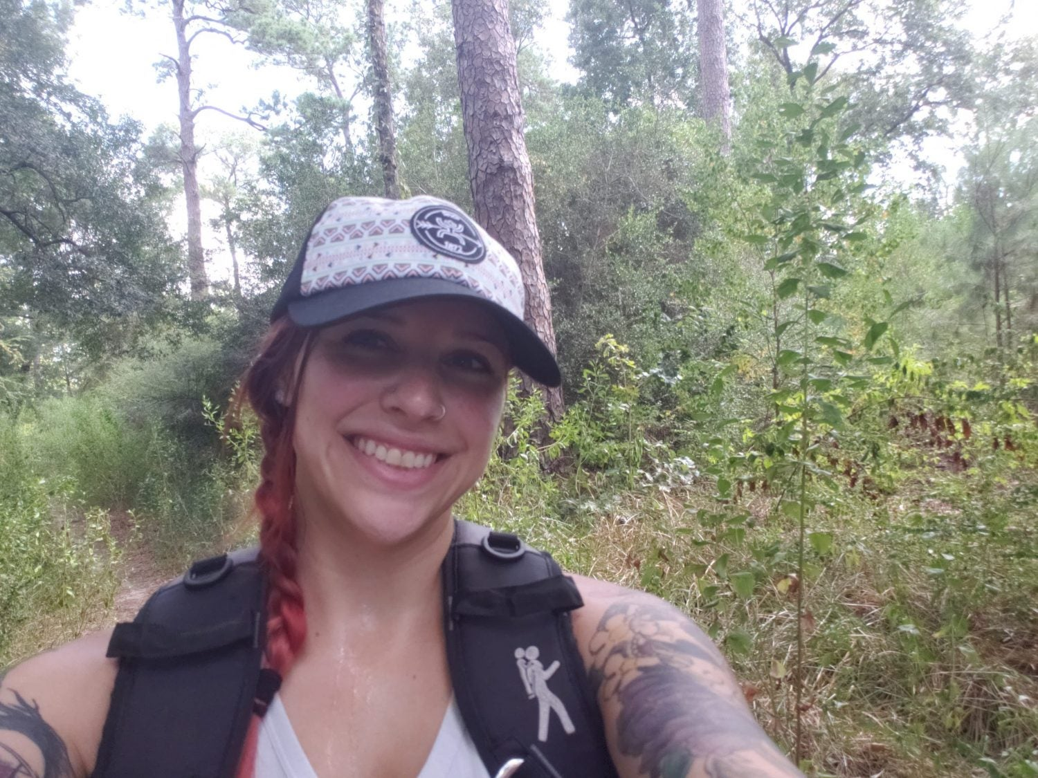 a female hiker poses for a selfie in the wilderness