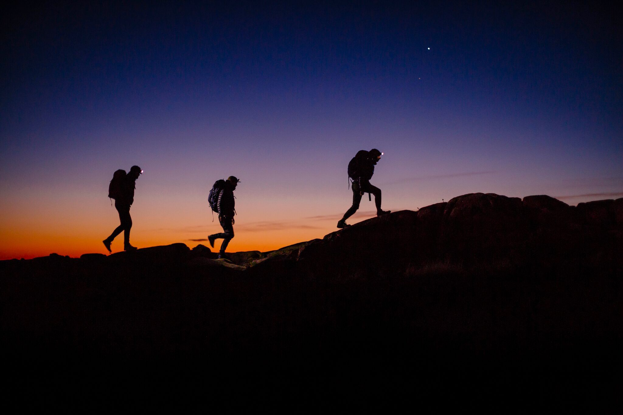 3 night hiking silhouettes at sunset