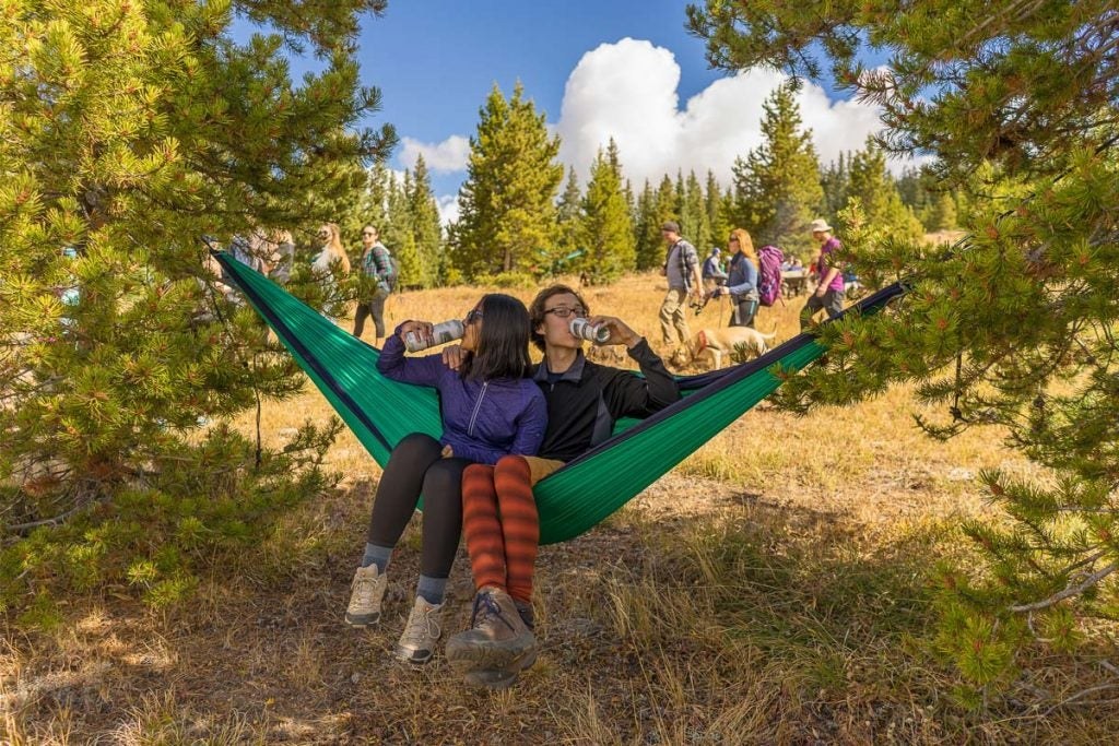 two friends share a hammock, drinking beer from colorado breweries