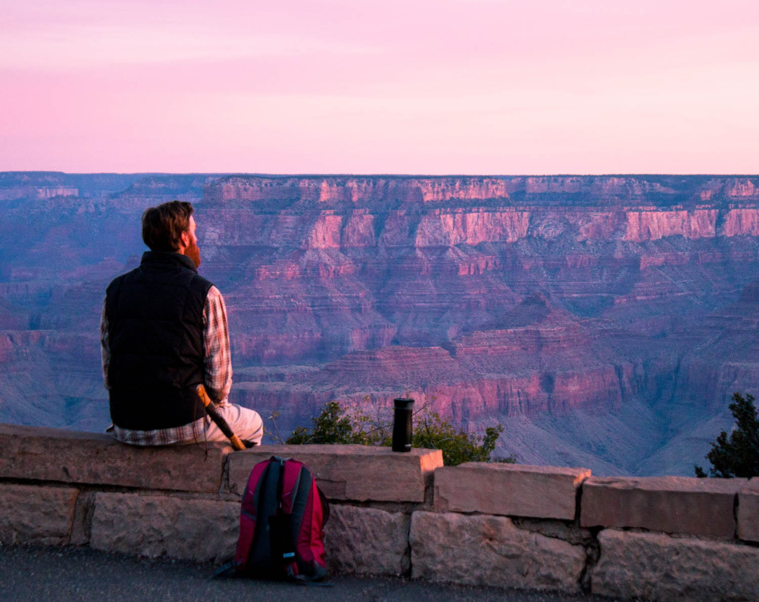 hiker rests on edge of platform as pink and purple sunset illuminates the grand canyon