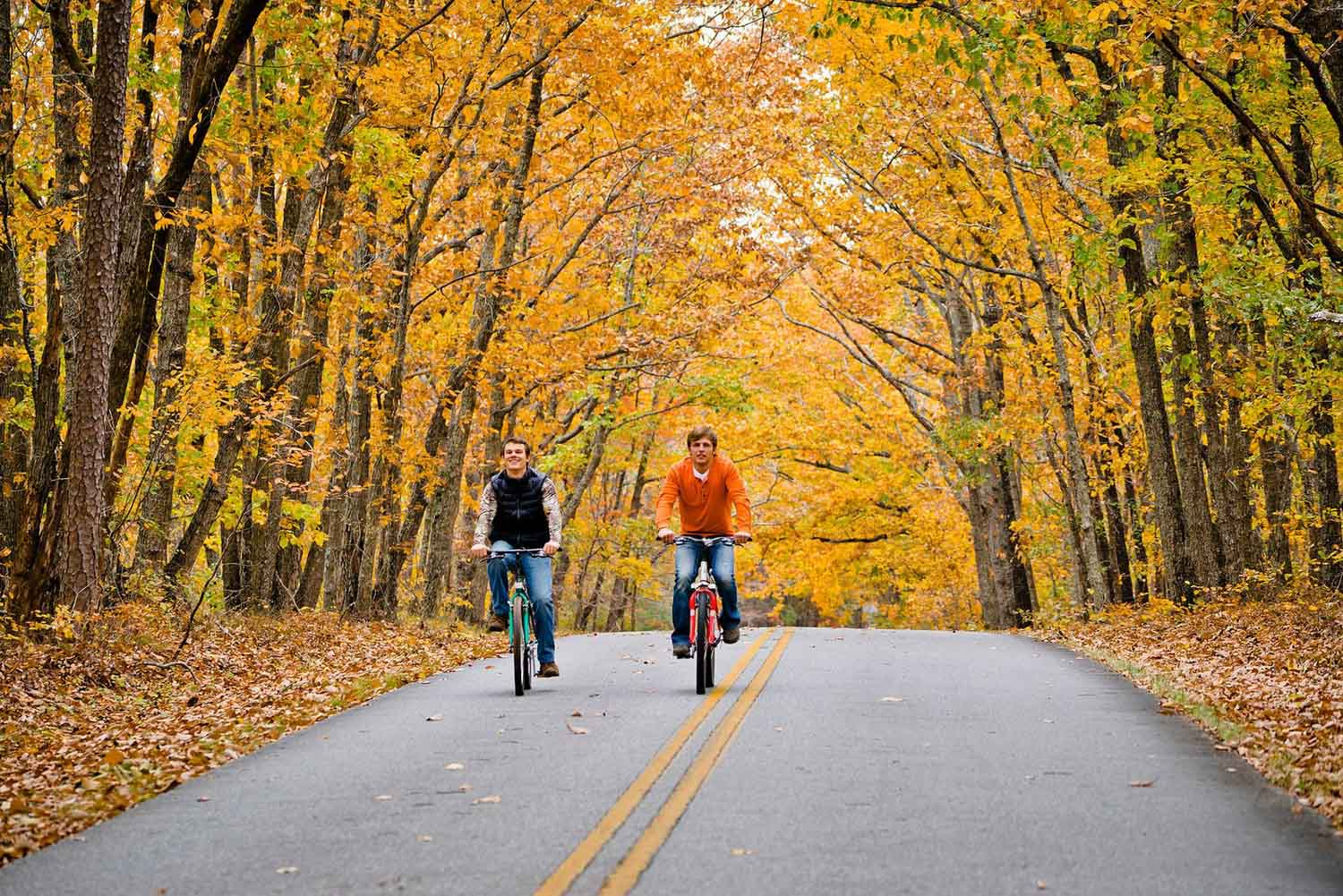 two bikers on a path through autumn leaves