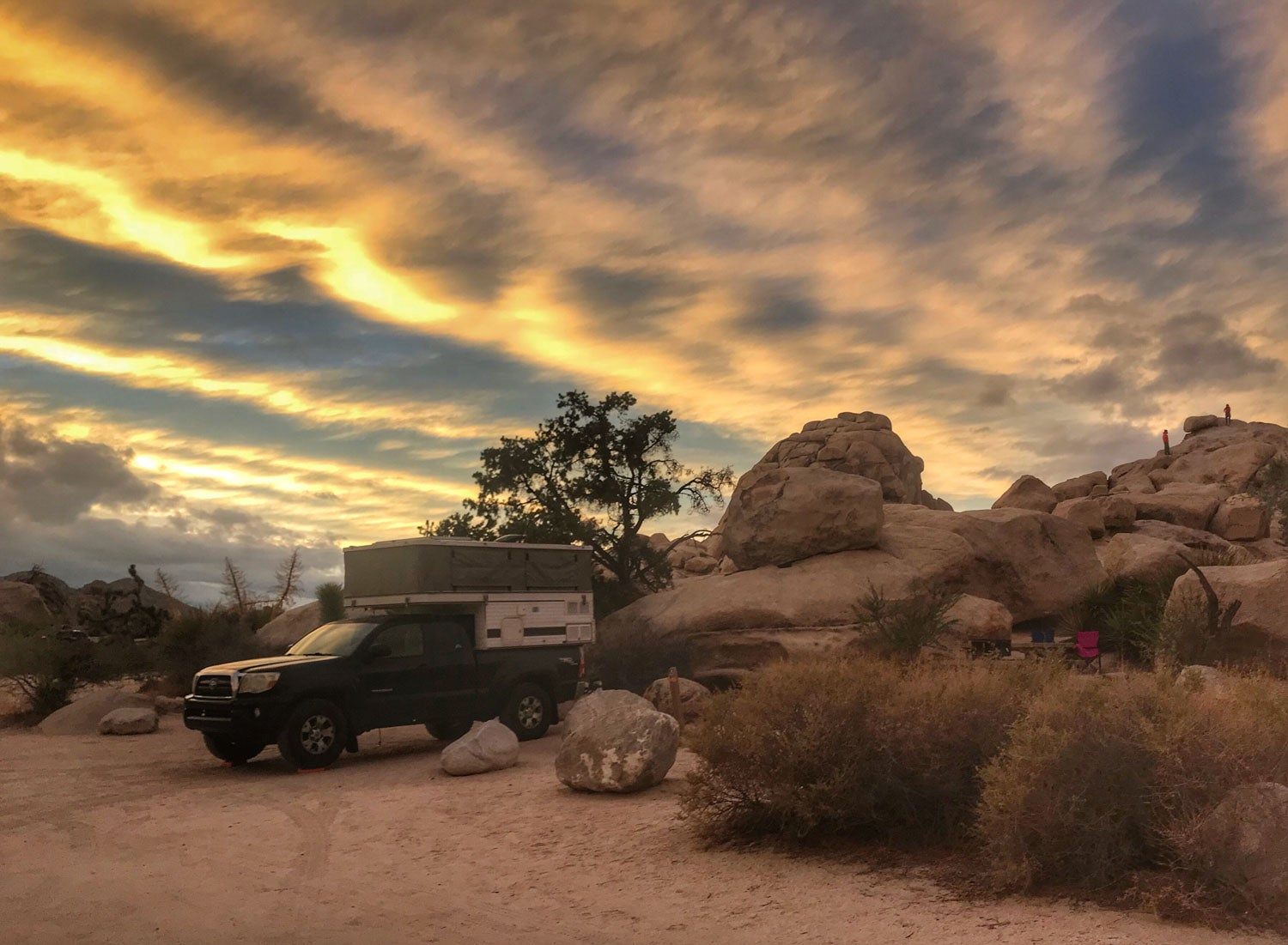 golden sunset illuminates rocks and truck camper at hidden valley campground in joshua tree national park
