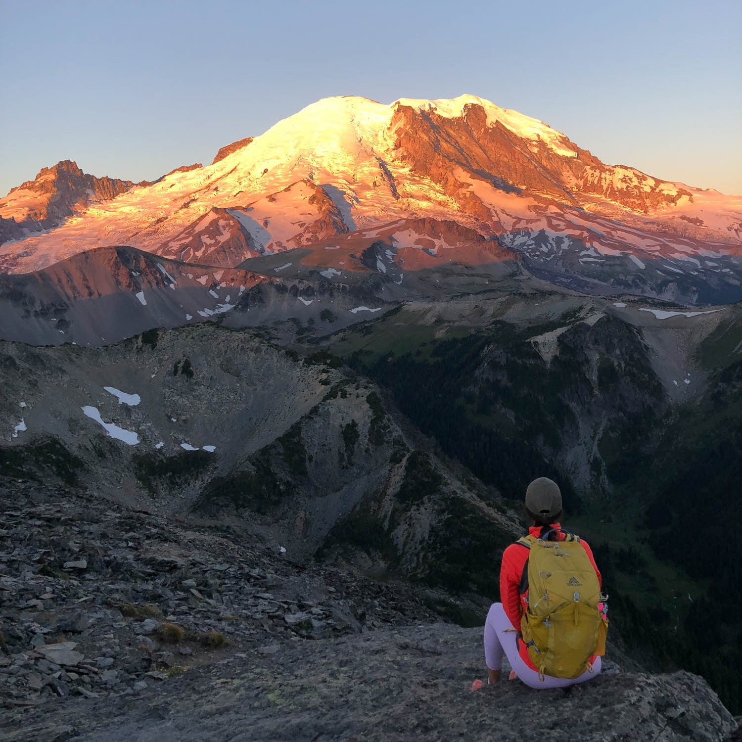 wonderland trail Hiker looking at Mount Rainier at sunset