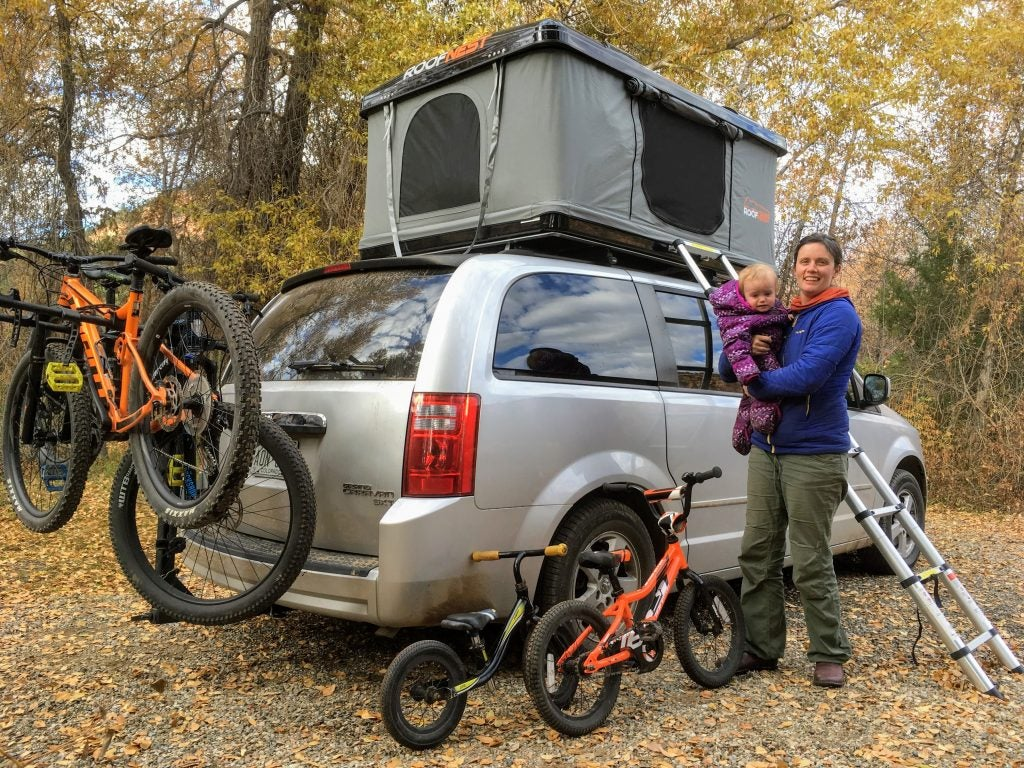 mom and daughter pose in front of roofnest tent installed on a mini van