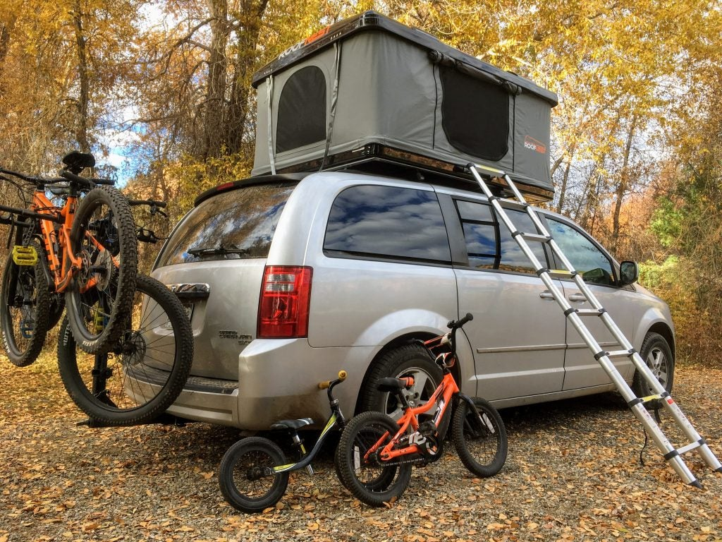 Roofnest hard shell rooftop tent set up on minivan with bikes