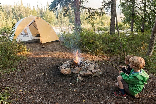 Kids roast smores by a fire near a yellow tent at ophir creek in alaska