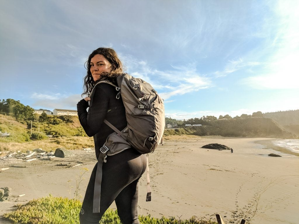 hiker with gregory backpack with beach and Oregon coast in the background