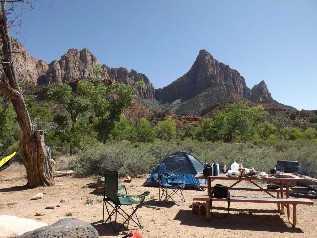 a tent and table are set up in front of rocky crags in the background seen from many zion national park hikes