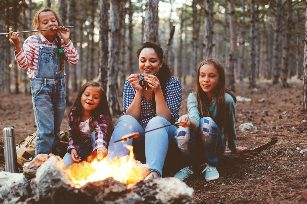 mom and three daughters roast marshmallows over the fire