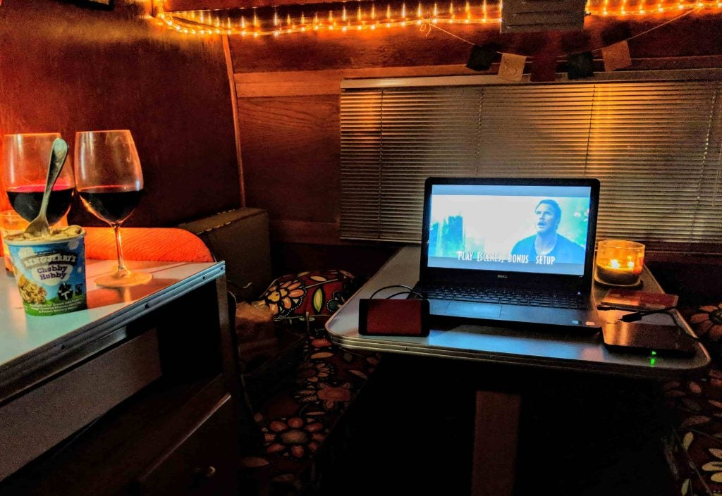 Wine glasses and ice cream pint beside a laptop playing a movie.