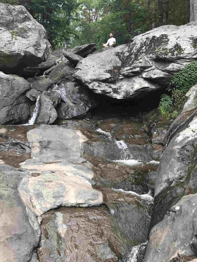 A man meditates at the top of Cunningham Falls