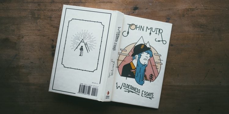 a motivational book by john muir rests open and face down