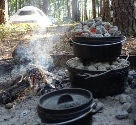 3 dutch ovens in a campfire with a tent in the background for a Thanksgiving camping trip