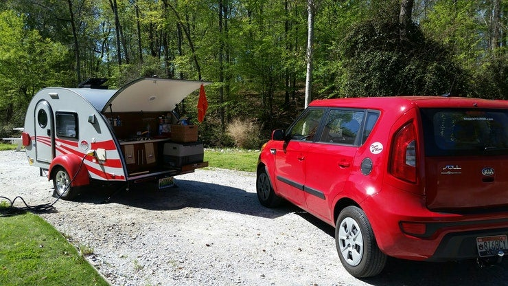 red kia soul parked next to a canned ham trailer