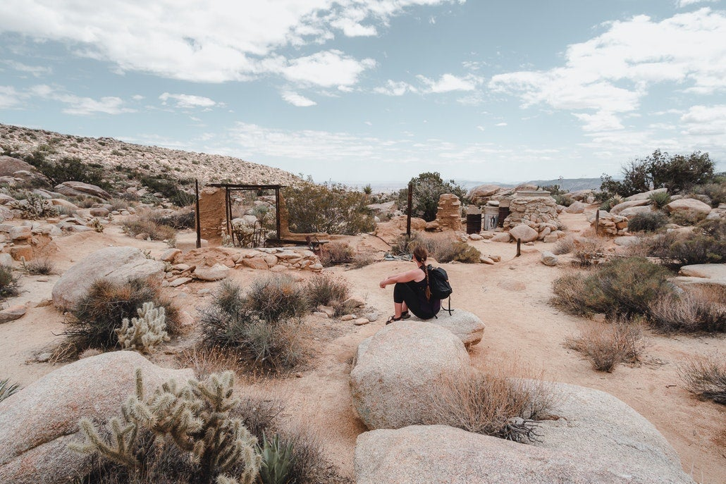 a woman rests on a rock near building ruins in a california desert