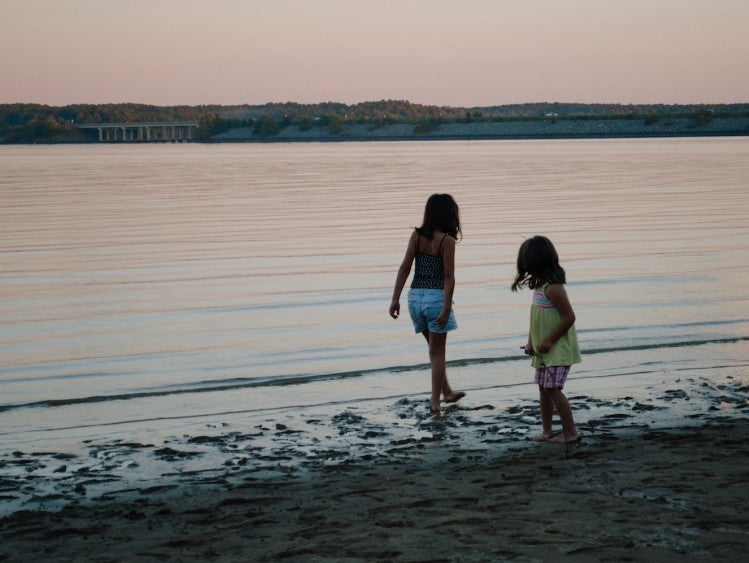 silhouette of two young girls playing in the water of Jordan Lake at sunset