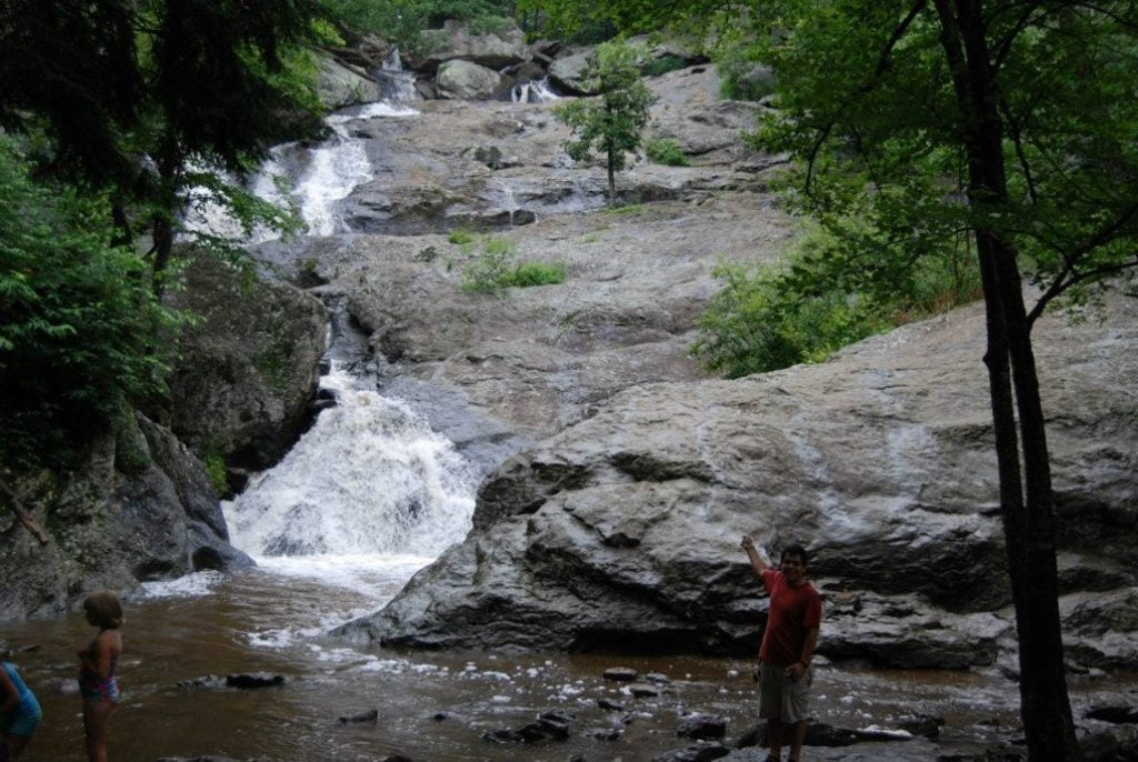 A man in the shade smiles and points toward a waterfall at Cunningham Falls State Park