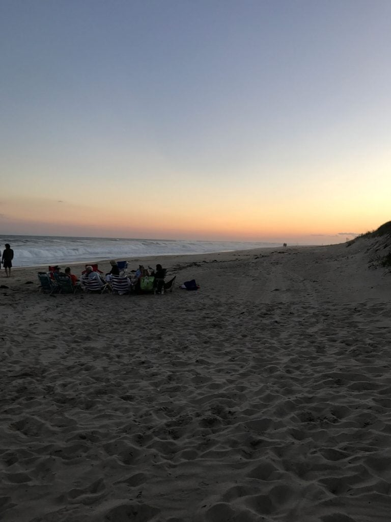 Campers relax on the beach of Hither Hills State Park during sunset.