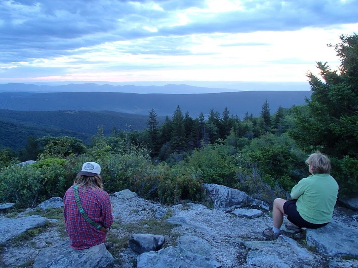 two hikers rest on rocky cliff overlooking a valley in the dolly sods wilderness area