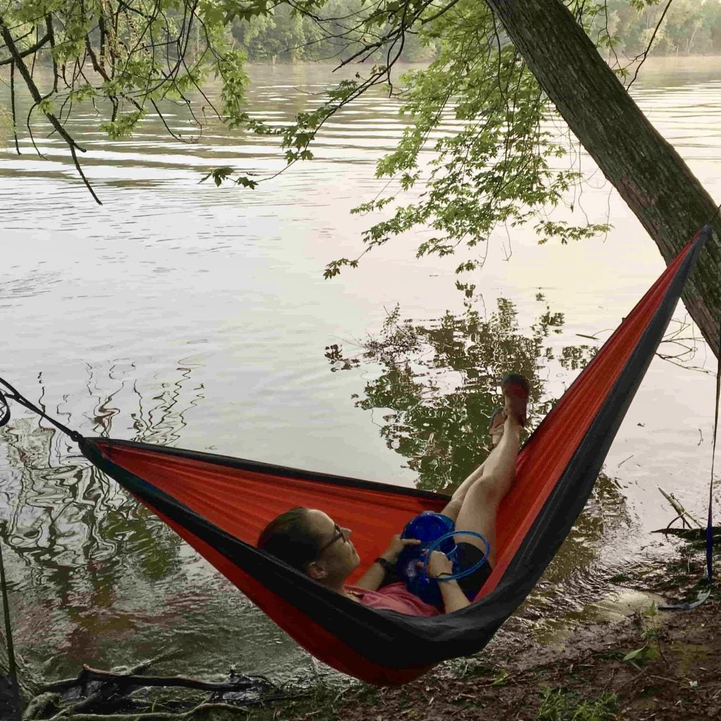 camper lounges in red hammock on riverfront