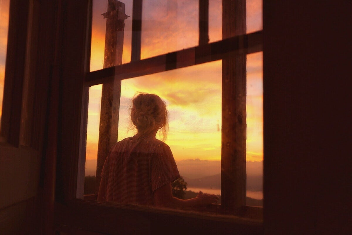 silhouette of a woman looking out the thorny mountain fire tower windows as an orange and pink sunset glows outside