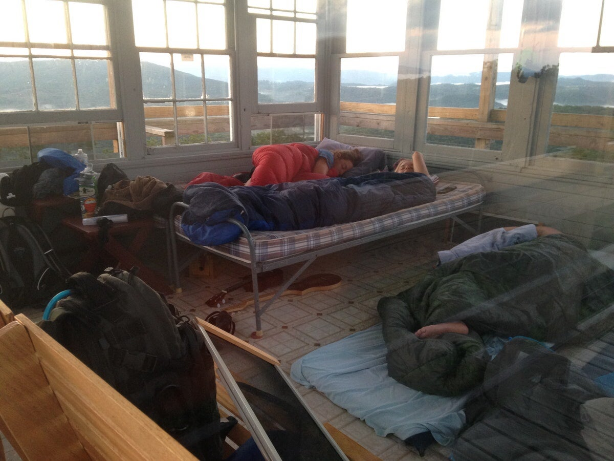 a group of campers sleep on cots in the thorny mountain fire tower