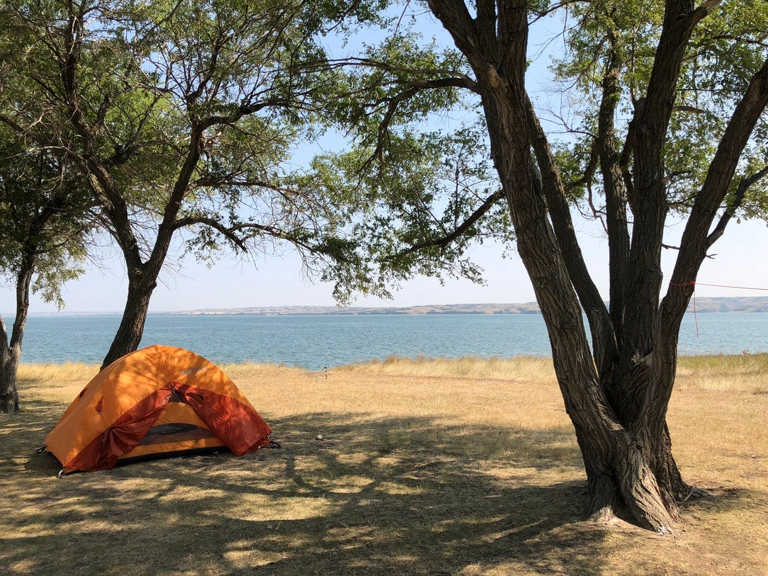 orange tent at lakeside campsite in one of north dakotas state parks