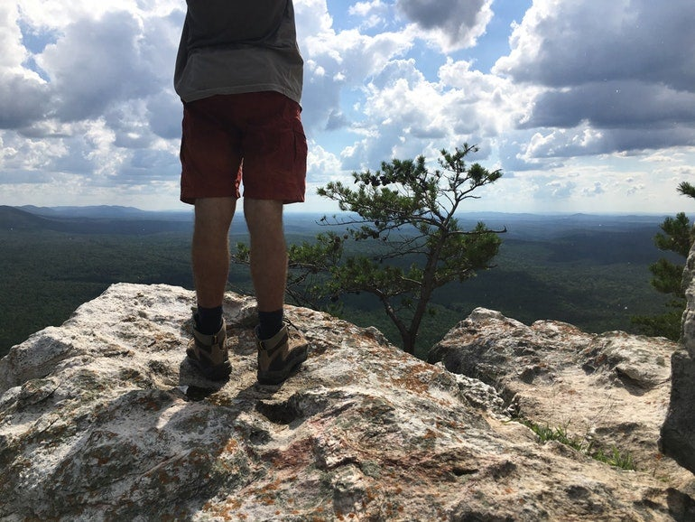 hiker stands atop rock formation on the pinhoti trail