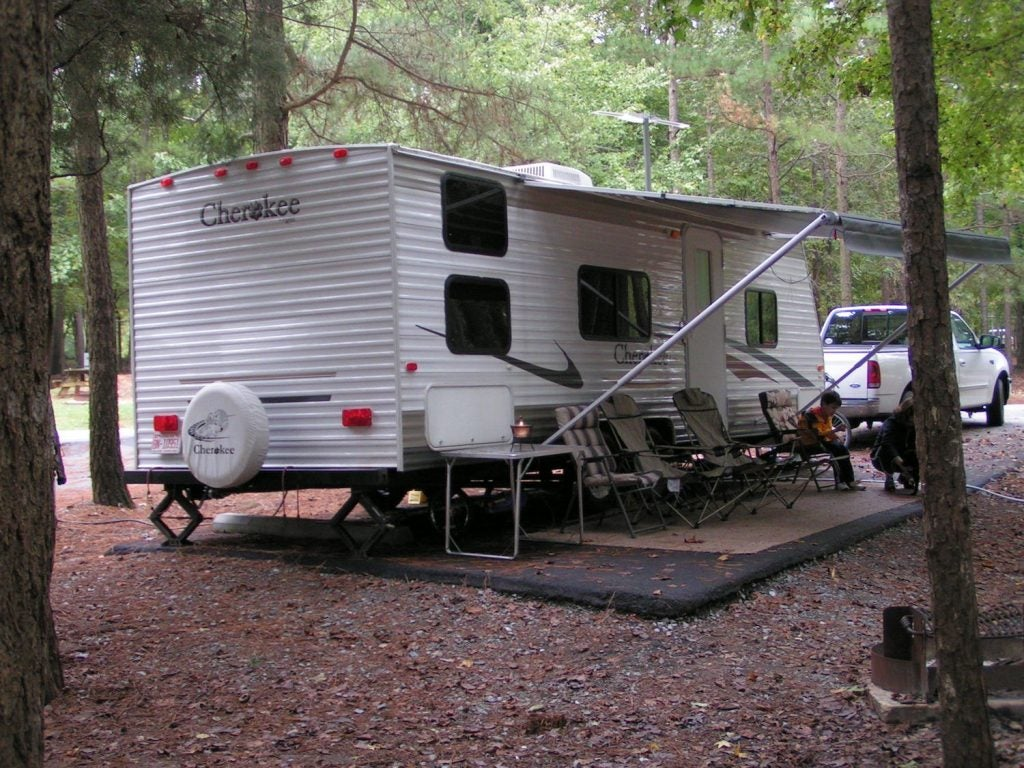 an RV at a wooded drive-in site at Cane Creek Park