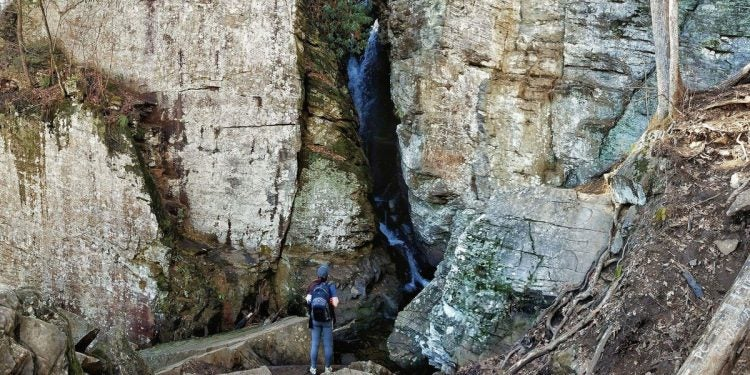 hiker stands below first tier of raven cliff falls
