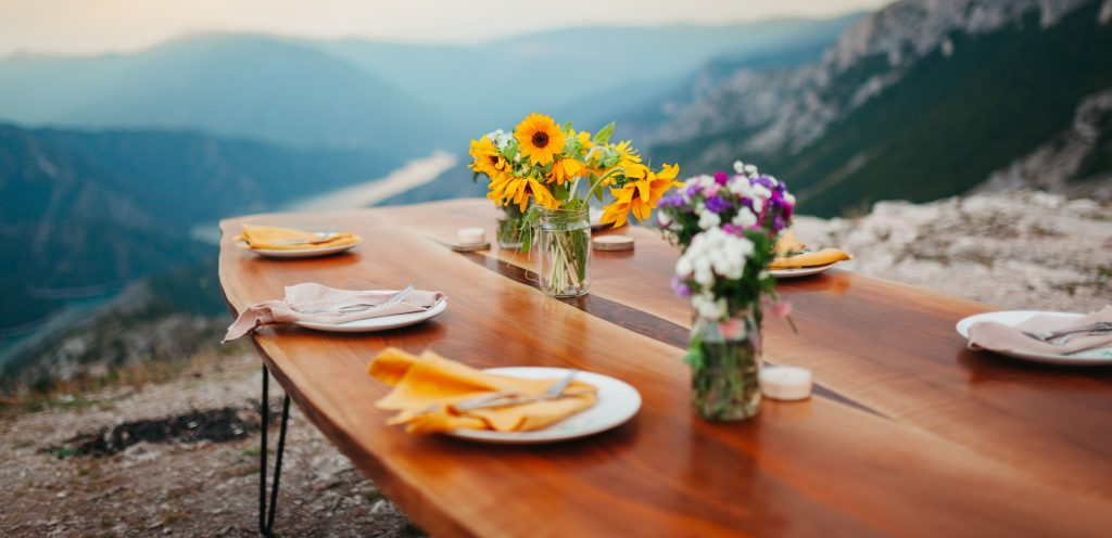Table setting in the mountains with sunflowers for a thanksgiving buffet celebration