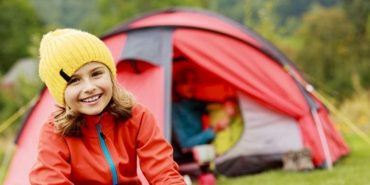 Smiling girl sits in campground with her kids camping gear