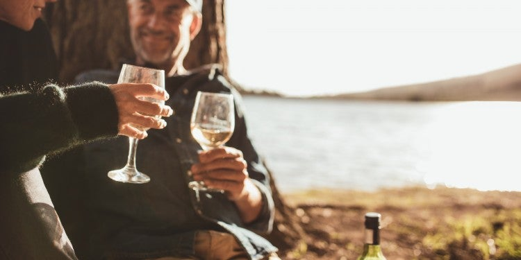 couple clinking two wine glasses together at their waterfront campsite