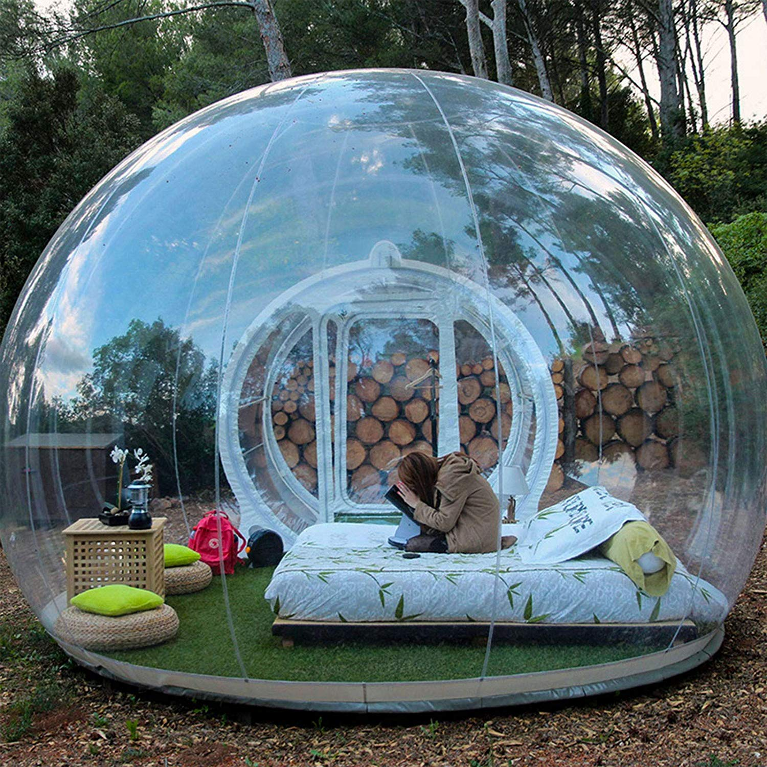 woman reads in a nicely furnished, clear inflatable bubble tent