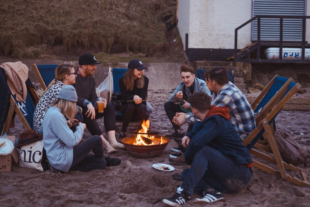 Group playing games that don't need wifi around a campfire