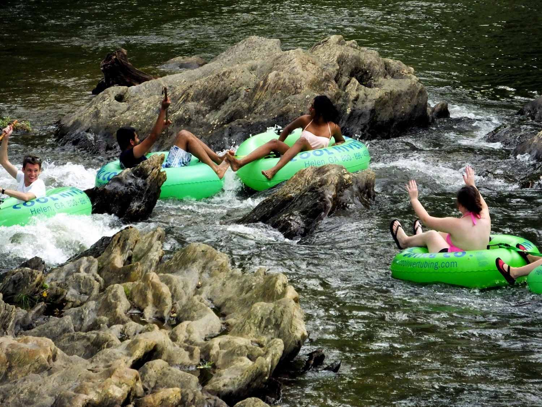 three bright green tubes enjoying Chattahoochee River tubing