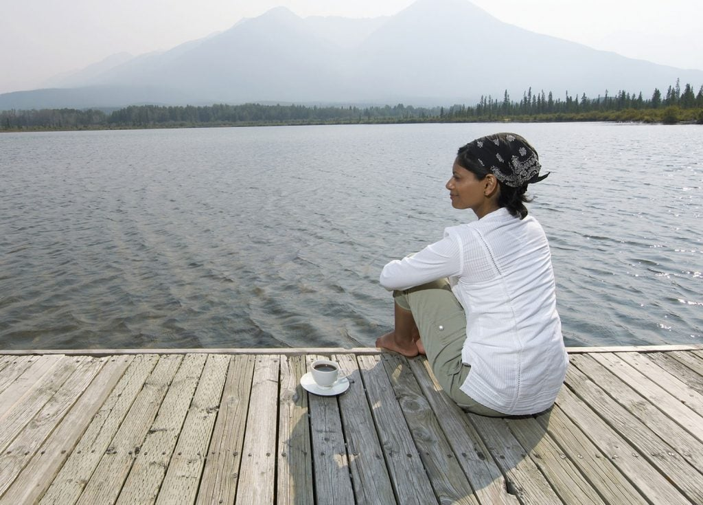 woman engaging in wilderness therapy on a lakeside dock