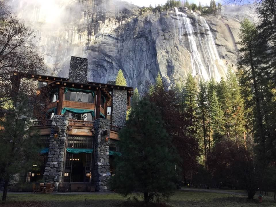 The Majestic Yosemite Hotel with rock face and waterfalls in background
