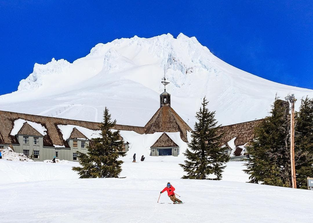 Mt. hood and the timberline lodge in the winter with skier in red jacket in foreground