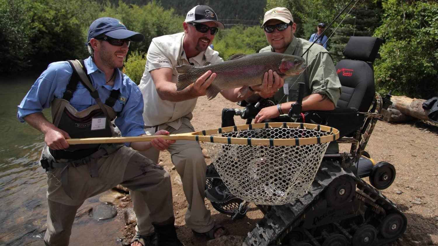 One man holds net as another holds a large rainbow trout, celebrating a veteran in a wheelchair who caught a fish