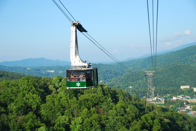 a gondola rises above the smokey mountains in gatlinburg, tennessee