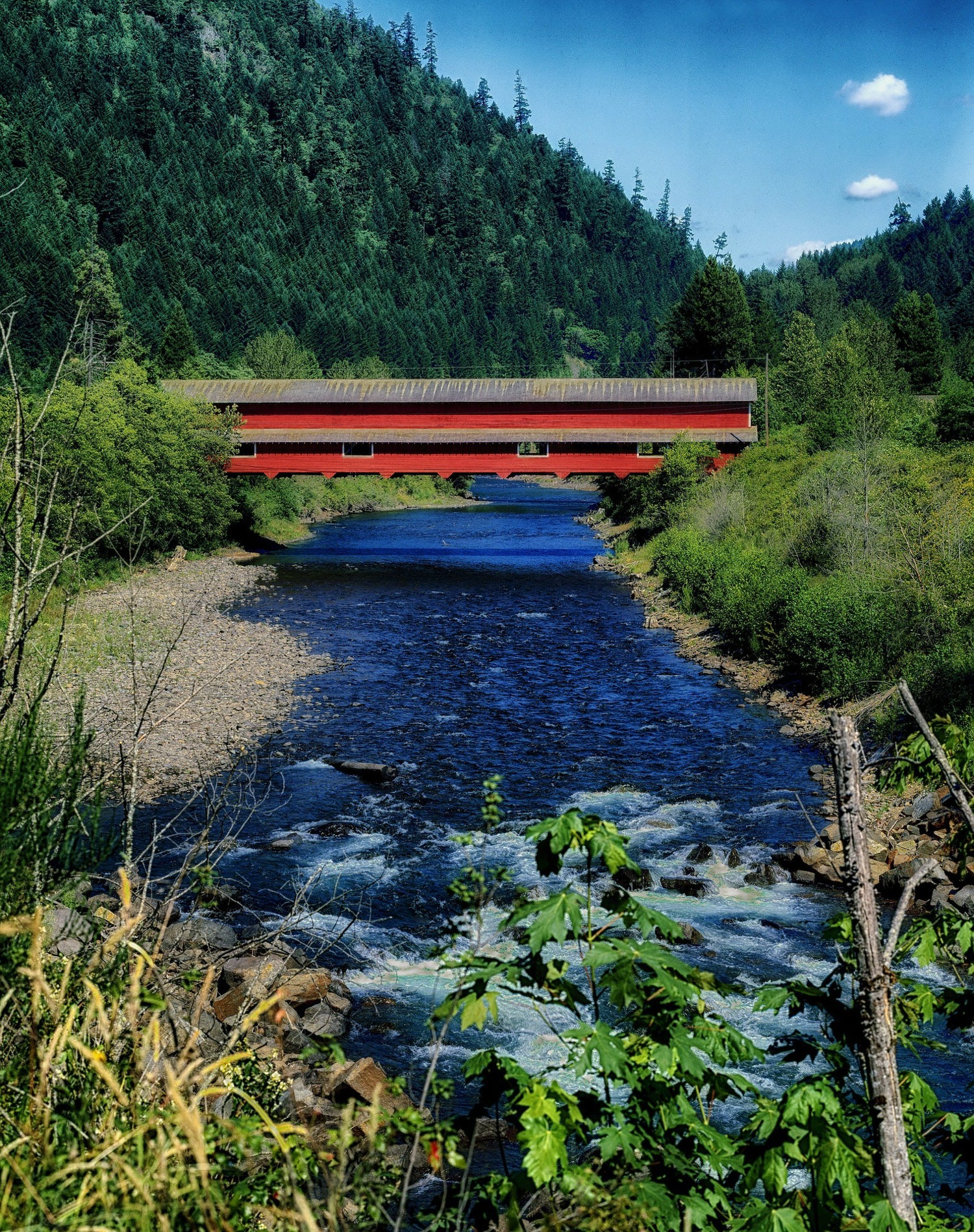 a Covered Bridge in Oregon over a blue river