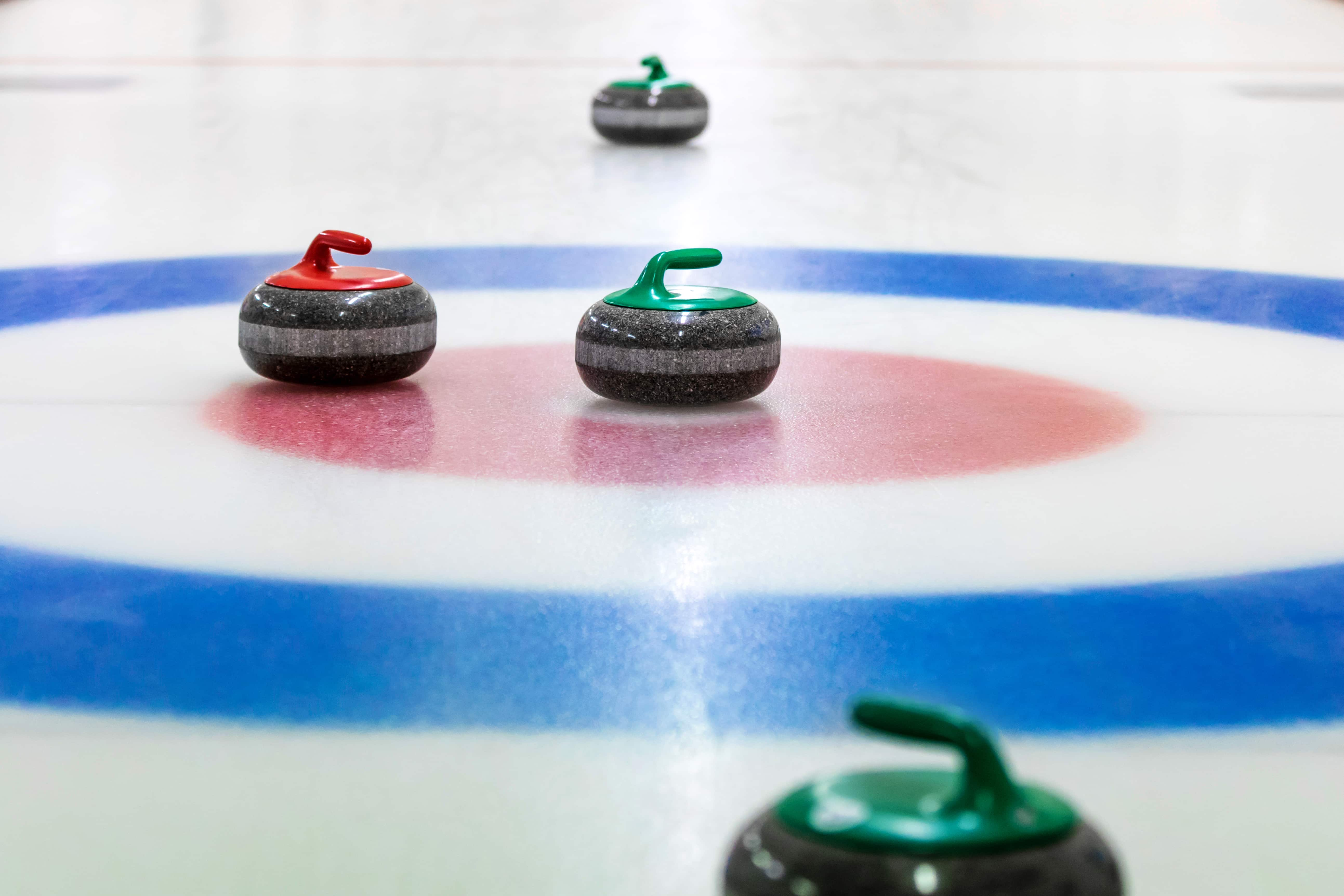 four curling stones are seen on a curling field, with one in the center of the target