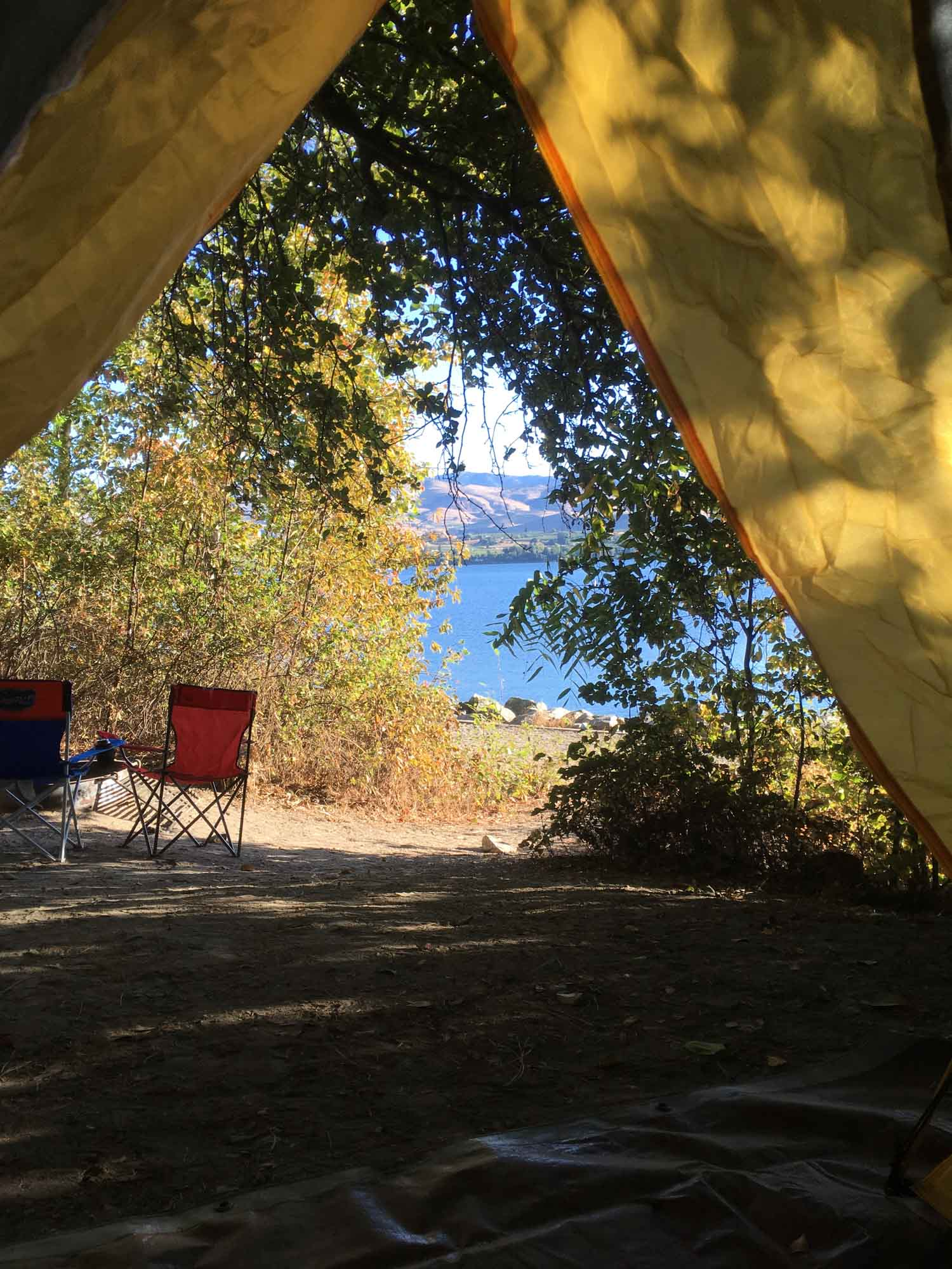 view from inside a tent of camp chairs in the forest beside a lak.