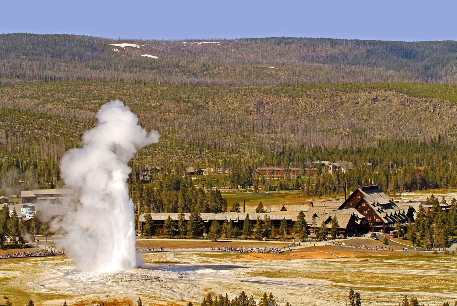 old faithful geyser erupting in foreground with old faithful inn and mountainside in the background